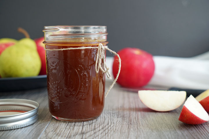 Jar of caramel sauce with apples in the background.