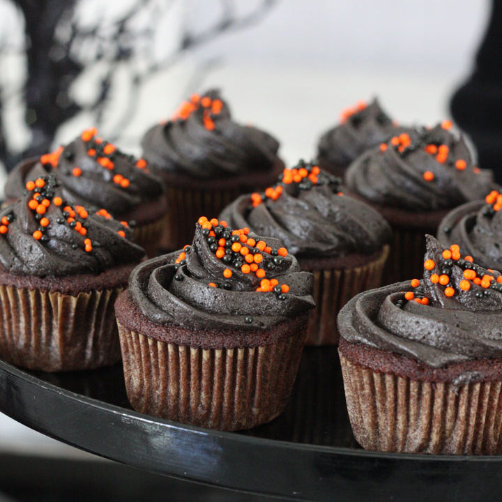 Chocolate cupcakes frosted with black frosting and orange and black sprinkles with halloween themed background.