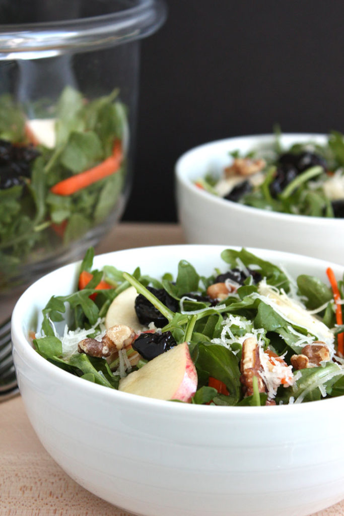 Fall arugula and apple salad in white bowl.