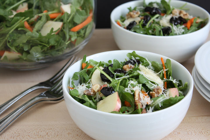 Fall and arugula apple salads in white bowls with forks.