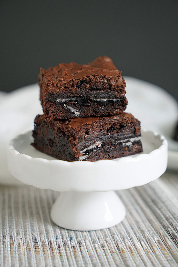 Oreo brownies stacked on a small white pedestal.
