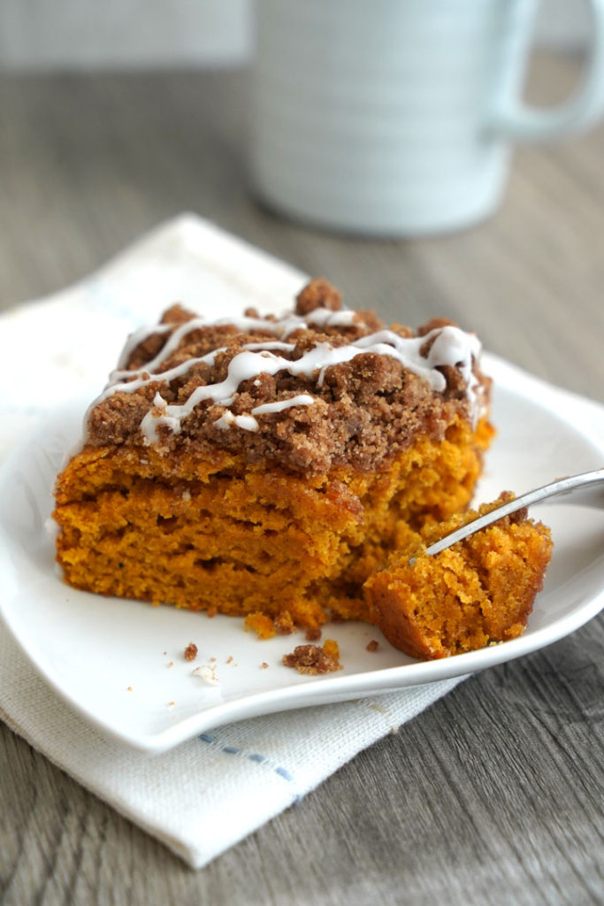 Pumpkin coffee cake piece on a white plate with fork.