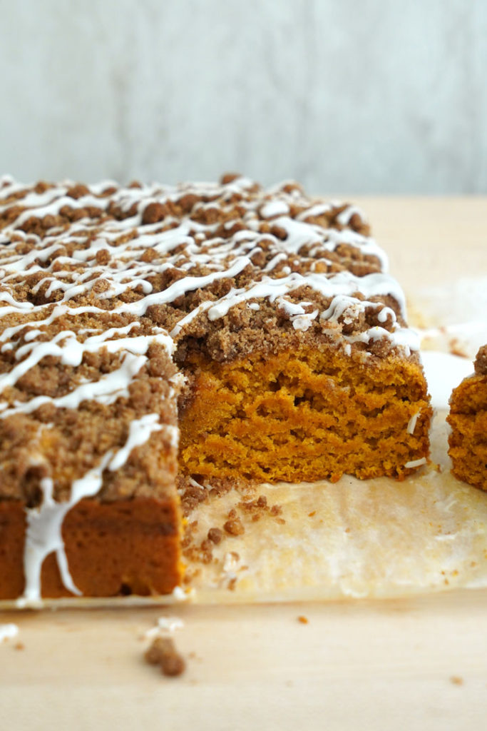 Pumpkin coffee cake with piece cut out of corner.