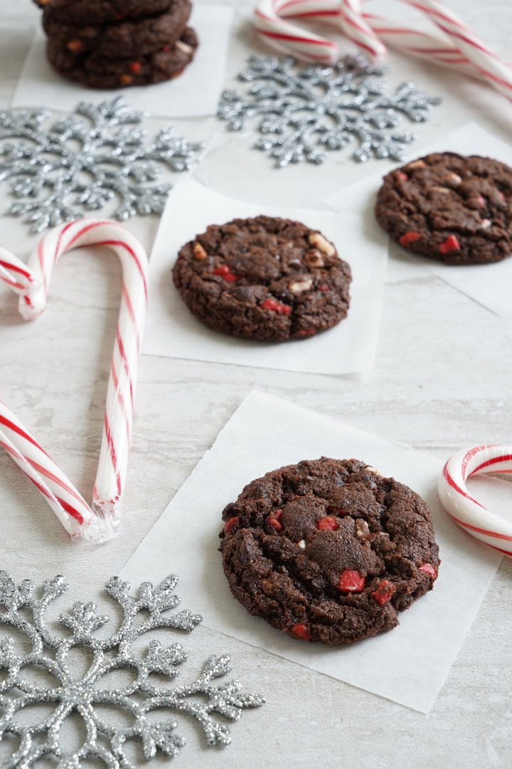 Chocolate peppermint chip cookies surrounded by candy canes and silver snowflakes.