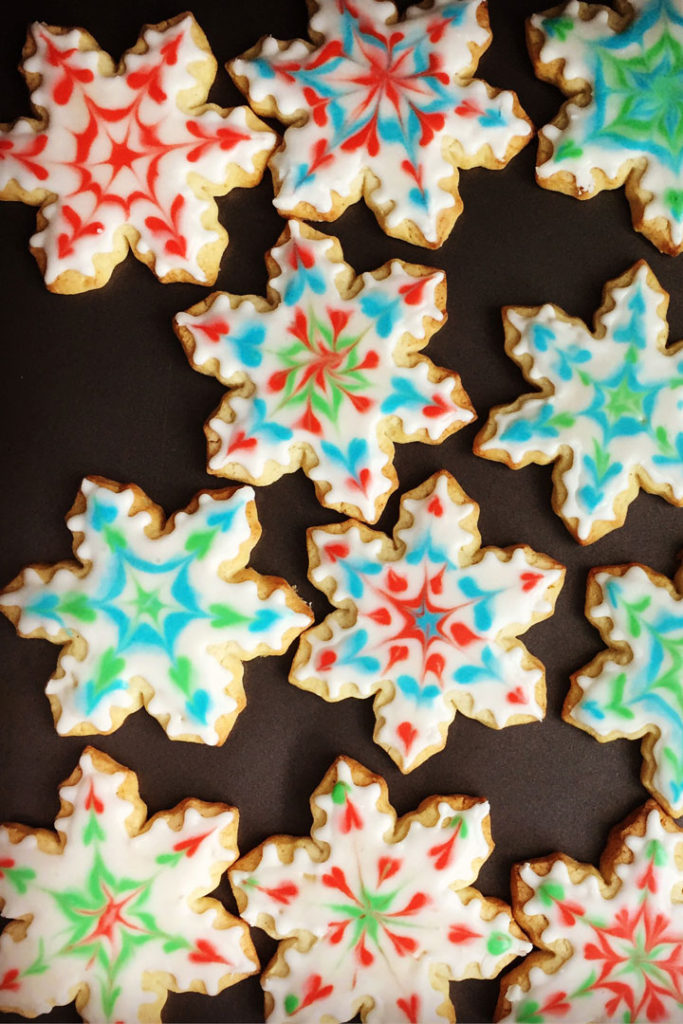 Snowflake shaped cookies decorated in various colors.