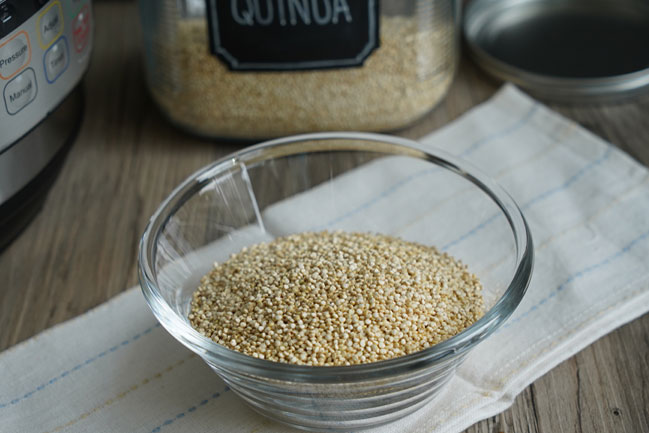 Dry uncooked quinoa in a clear glass bowl.