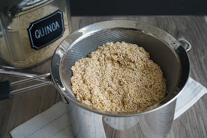 Rinsed quinoa in a strainer, draining over a pot.