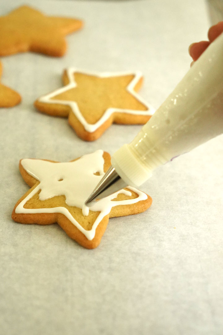 Star shaped sugar cookies being decorated with royal icing.