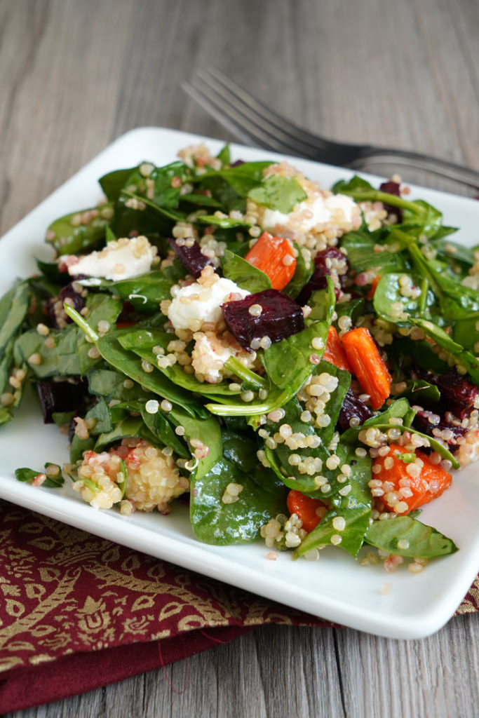 Spinach, roasted beets and carrots, quinoa salad on a white plate.