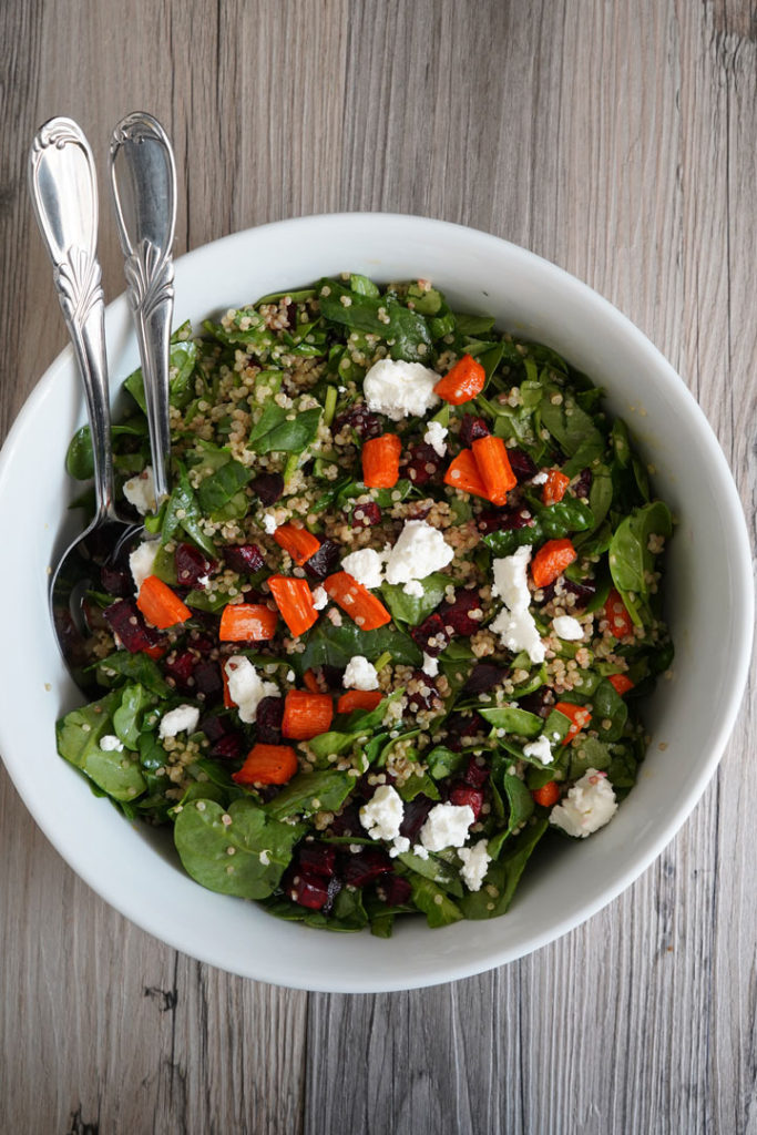 Spinach, roasted beets and carrots, quinoa salad in a large bowl.