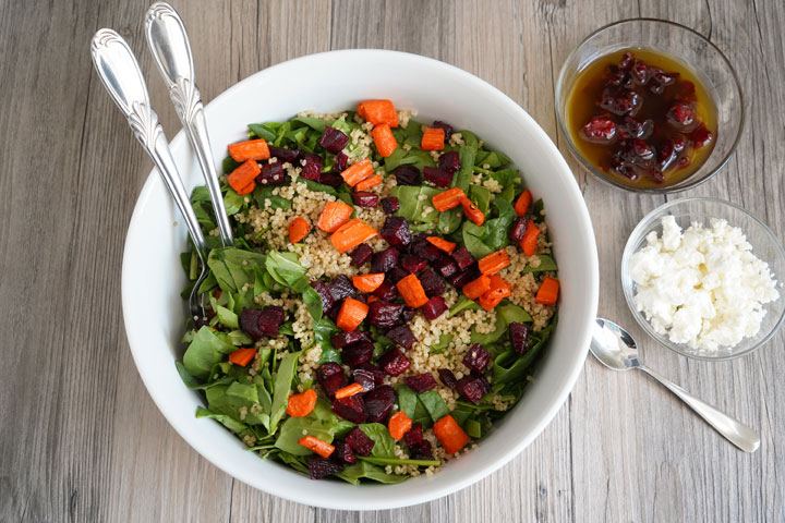 Spinach, roasted beets and carrots, quinoa salad being mixed in a large bowl.