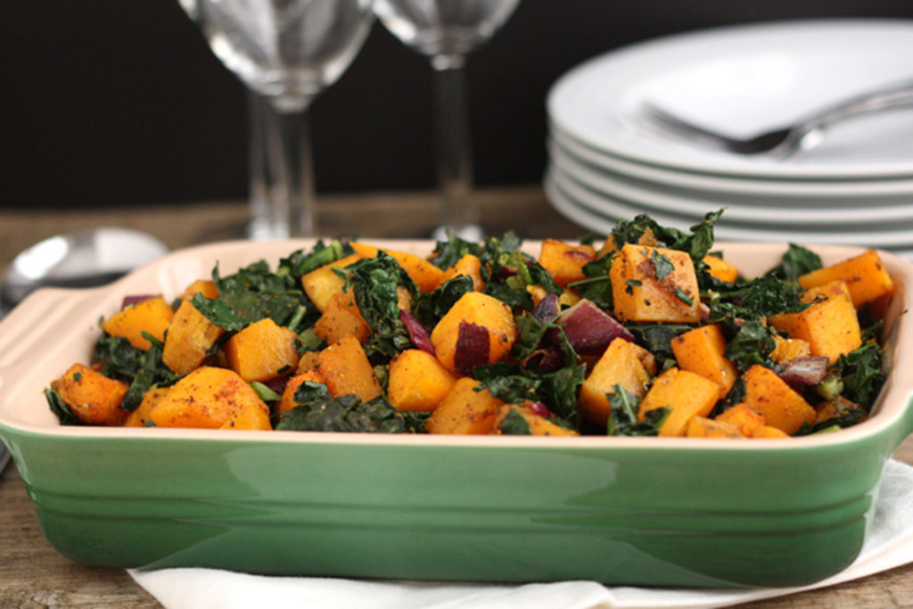 Spicy butternut squash with kale and red onion in a green serving dish.