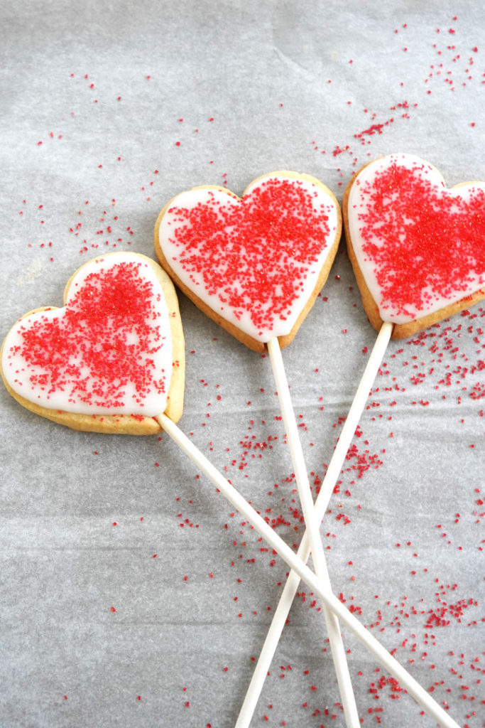 Heart shaped sugar cookies with red sugar crystals on a stick.