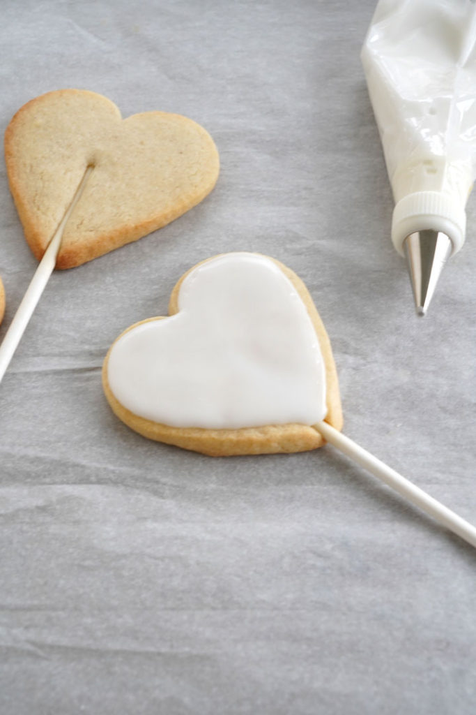 Baked heart shaped sugar cookie dough attached to a stick with icing.