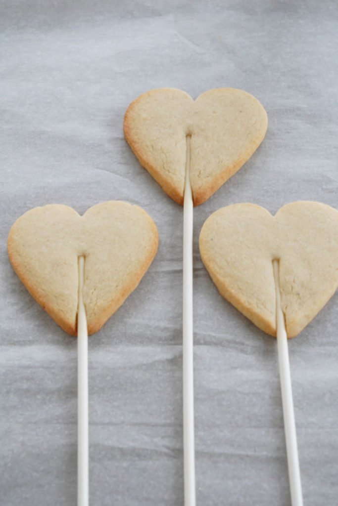 Baked heart shaped sugar cookie dough attached to a stick.
