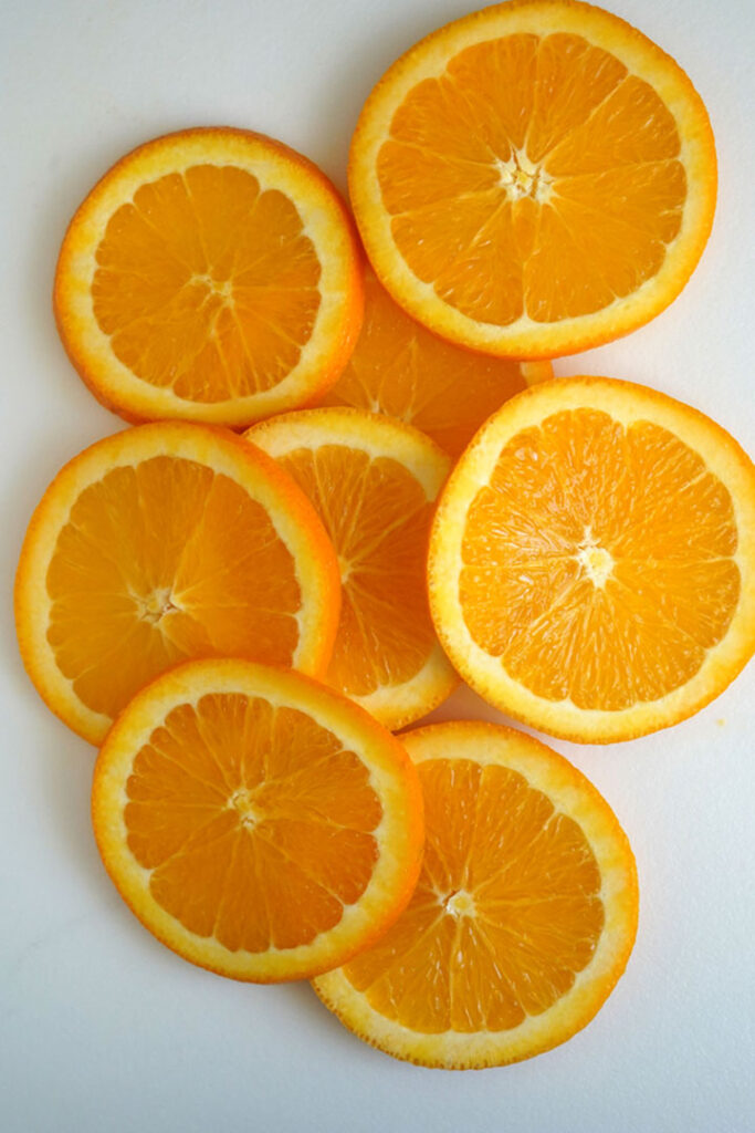 Round orange slices on a white cutting board.