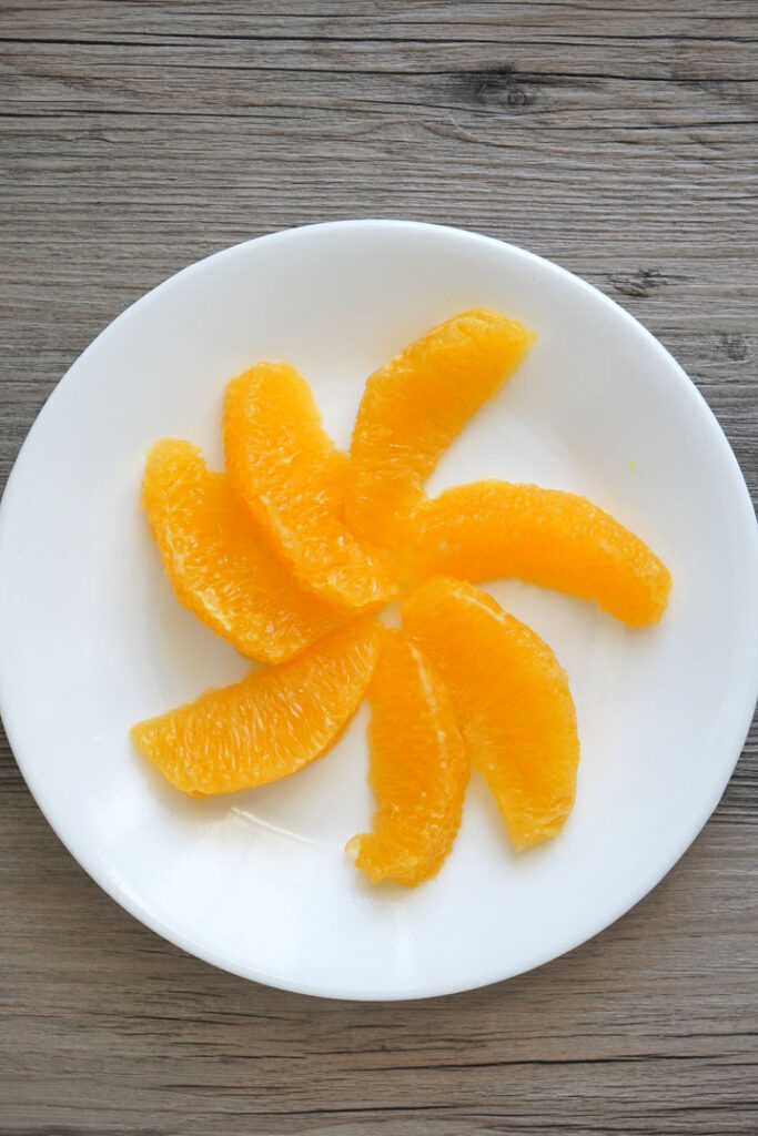 Segemented orange slices on a white plate.