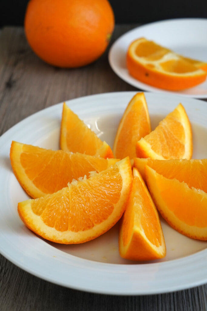 Sliced orange wedges in a white plate.