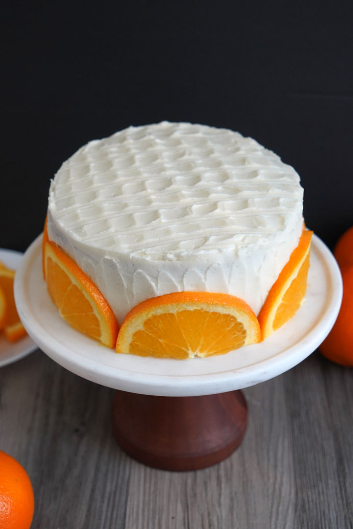 Orange cake with cream cheese frosting and fresh orange slices shown on a wood pedestal.