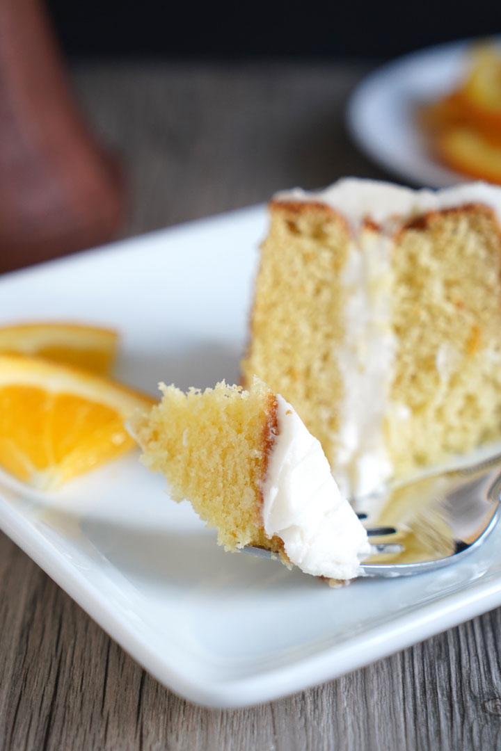 Orange flavored cake with cream cheese frosting on a fork with slice in the background.