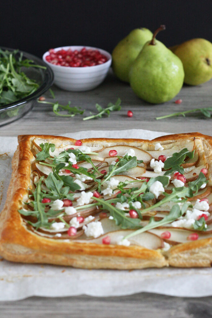 Pears baked on puff pastry with arugula, pomegranate, and goat cheese sprinkled on top. Pears in background.