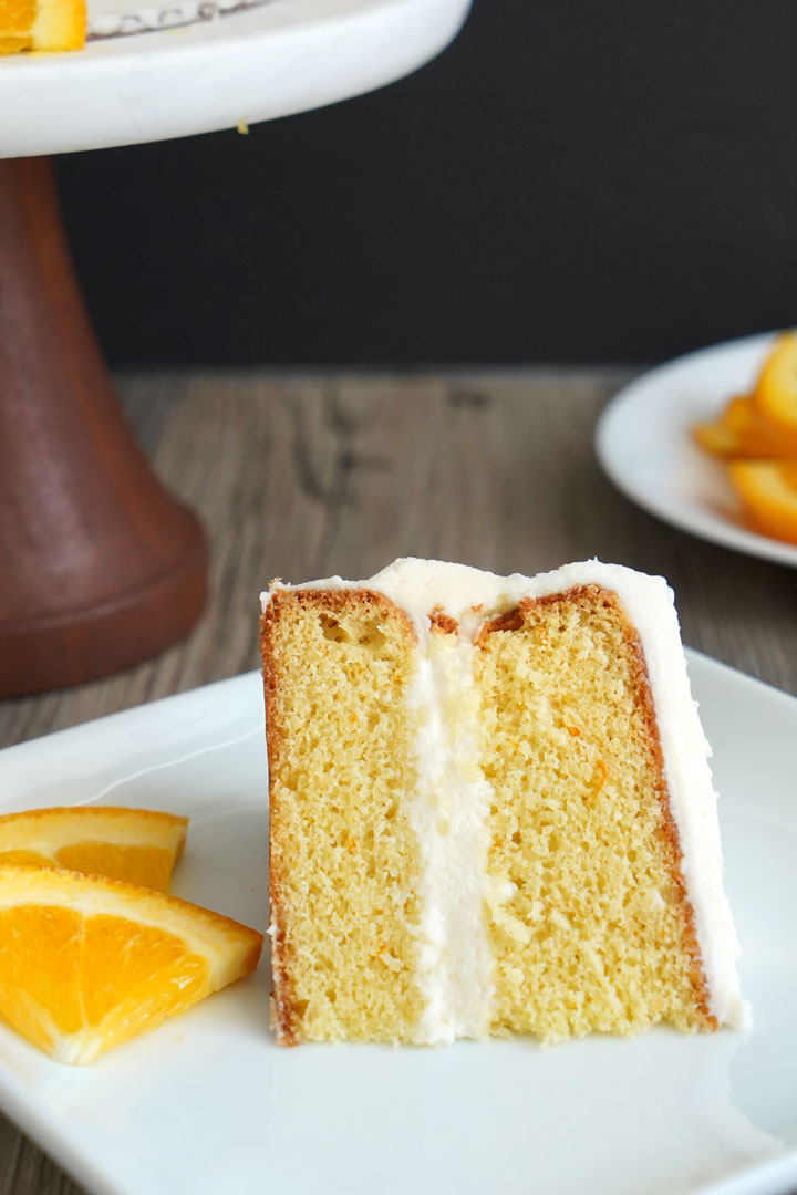 A slice of cake on a white plate. Orange slices on the side.