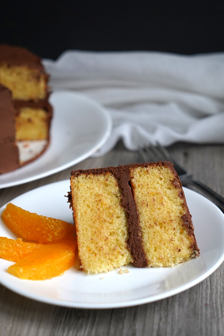 Chocolate frosted orange flavored cake slice on a white plate with segmented orange slices on the side.