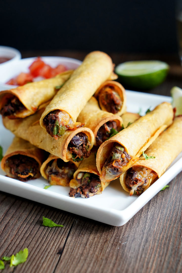 Bean and cheese taquitos stacked on a white plate