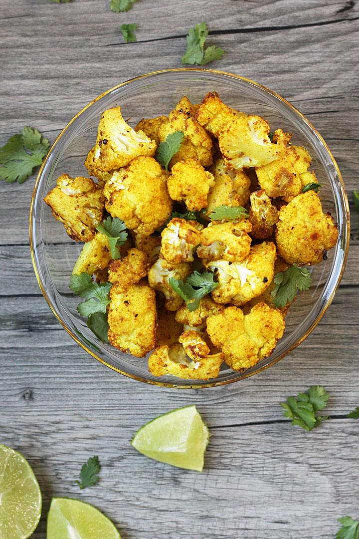 Roasted Cauliflower with turmeric in a clear glass bowl with cilantro and lime on the sides.