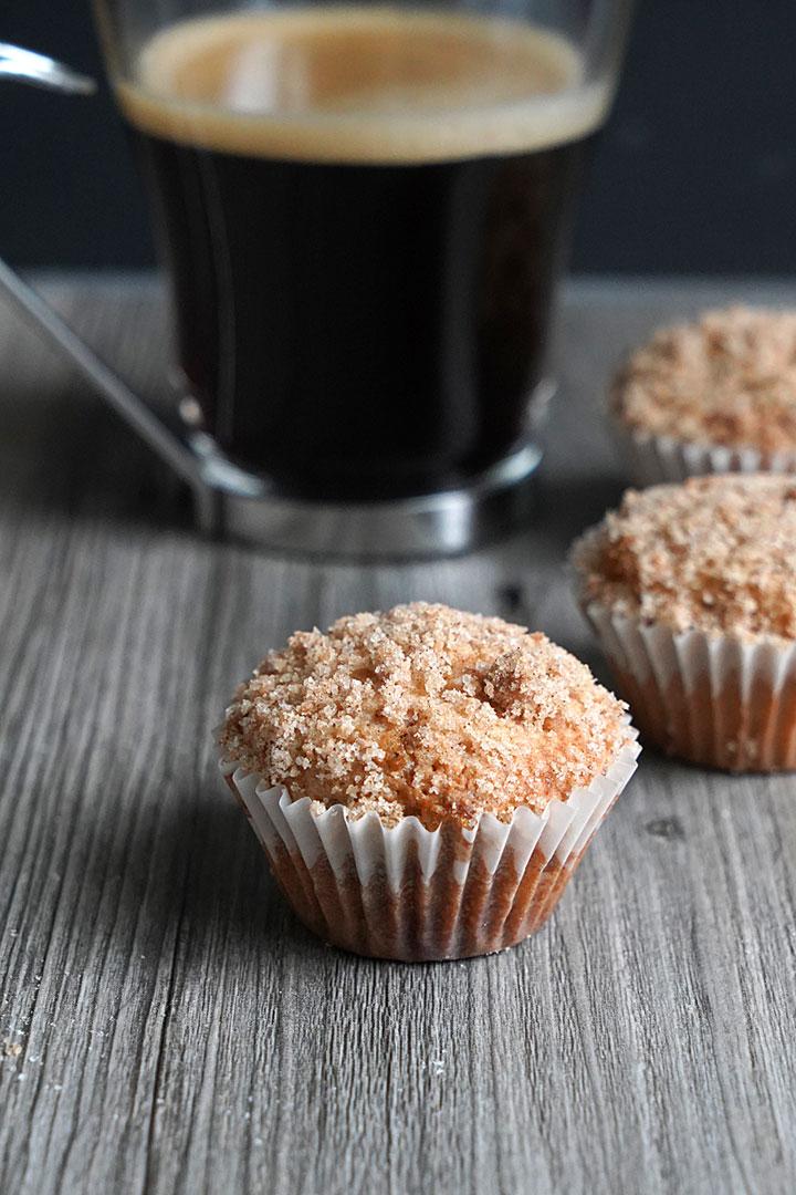 Mini coffee cake muffin with coffee mug in background.