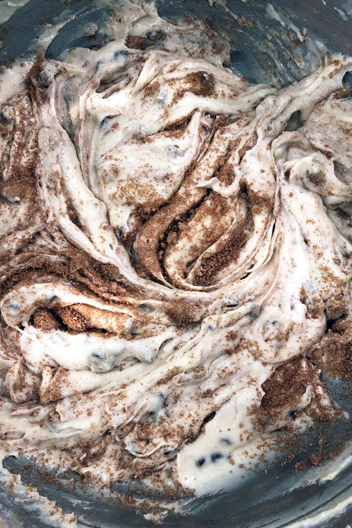 Muffin batter showing swirls of cinnamon filling.