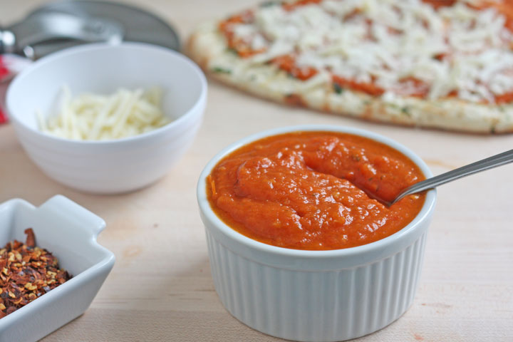 Pizza sauce in a bowl with pizza and cheese in background.