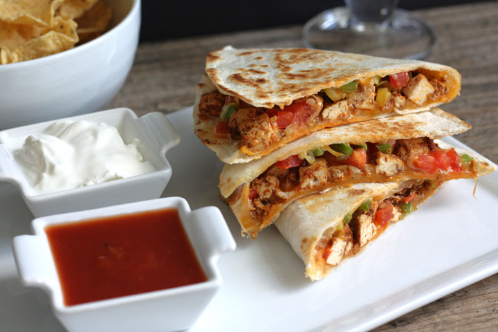 Tofu quesadillas served with salsa and sour cream.