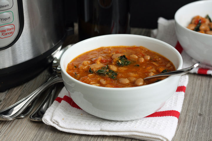 A bowl of cannellini bean soup on red and white napkin.
