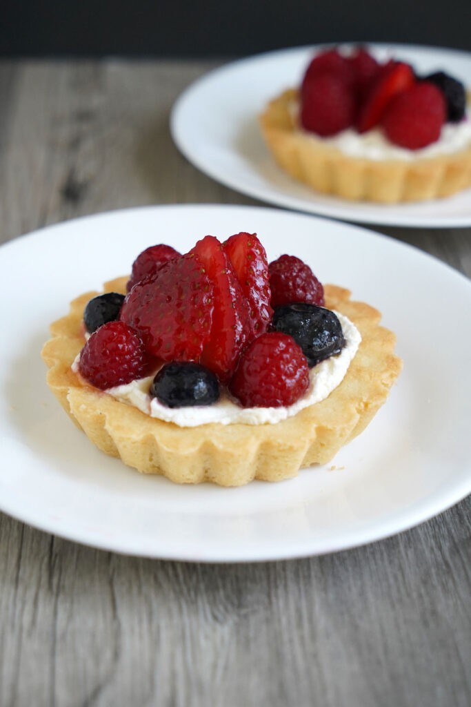 A fruit tart with strawberries, raspberries and blueberries on a white plate.