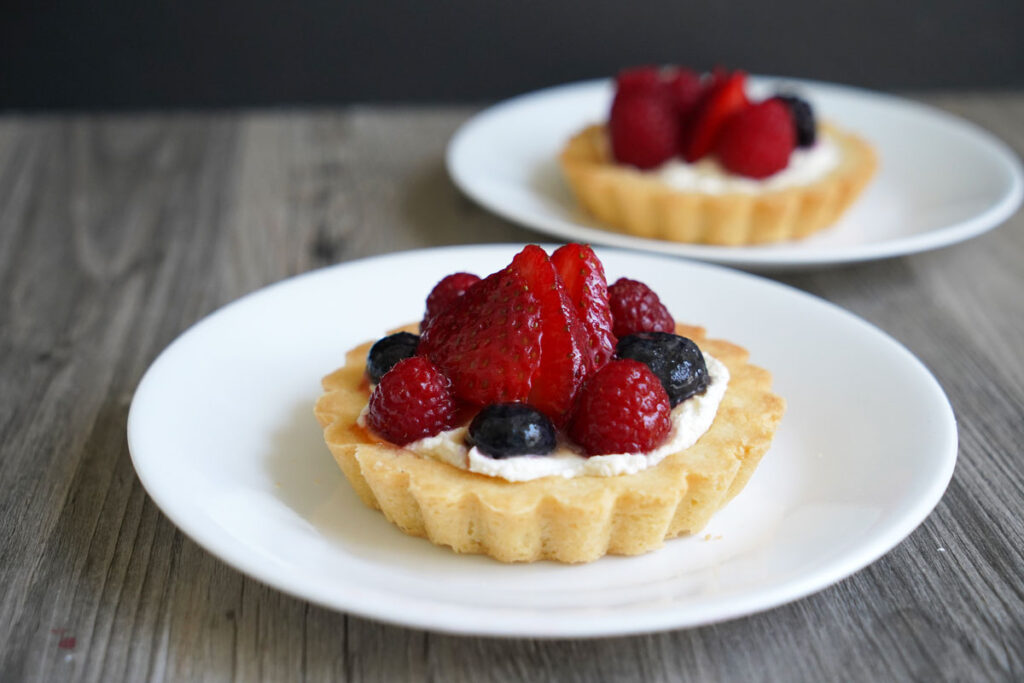Two plates of berry fruit tarts.