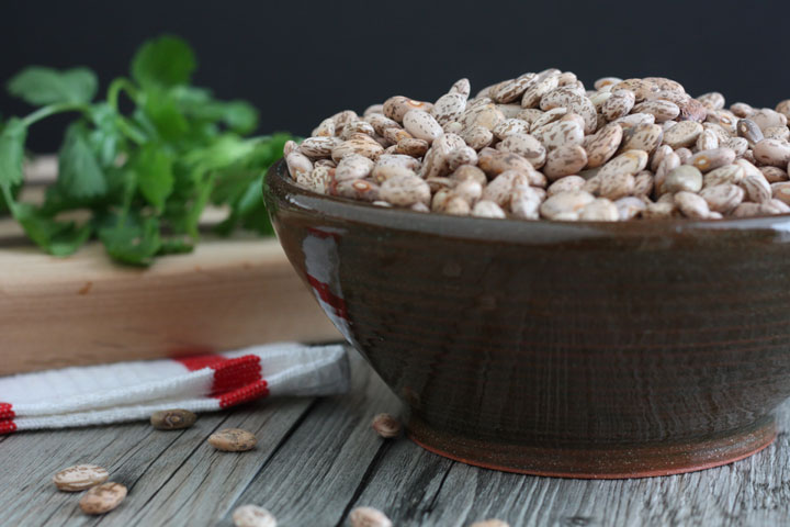 Dry pinto beans in a bowl.