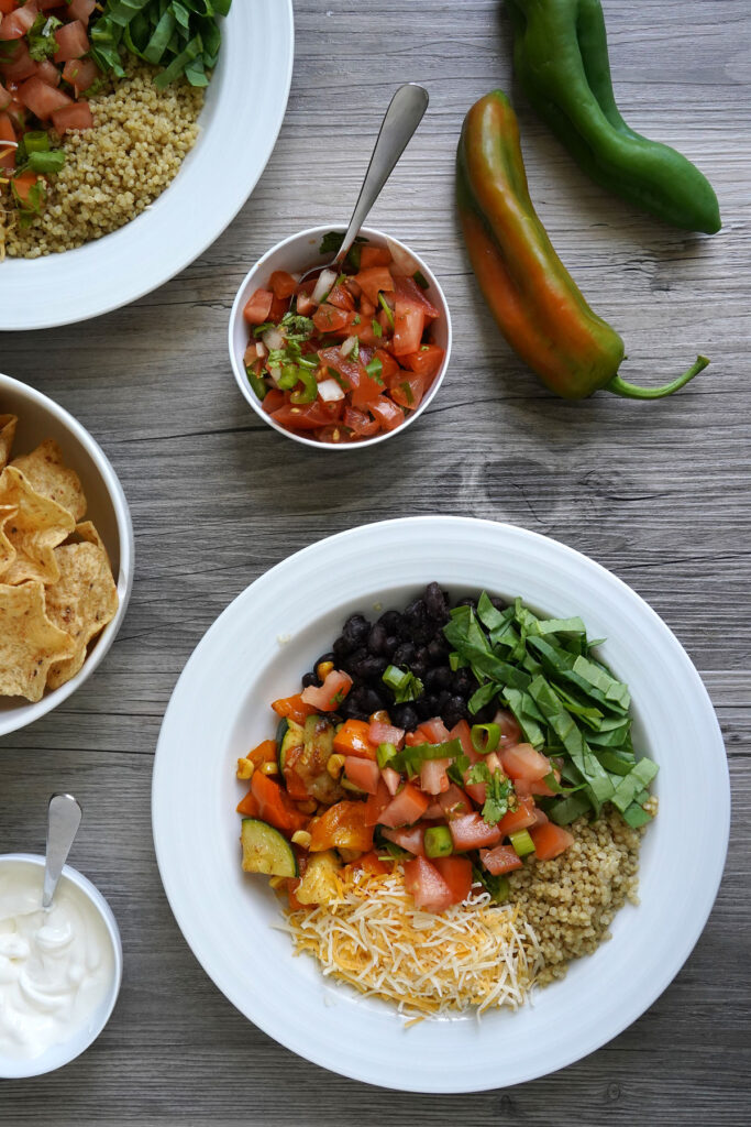 Bird's eye view of quinoa bowl on table with sides of fresh salsa, chips, and sour cream.