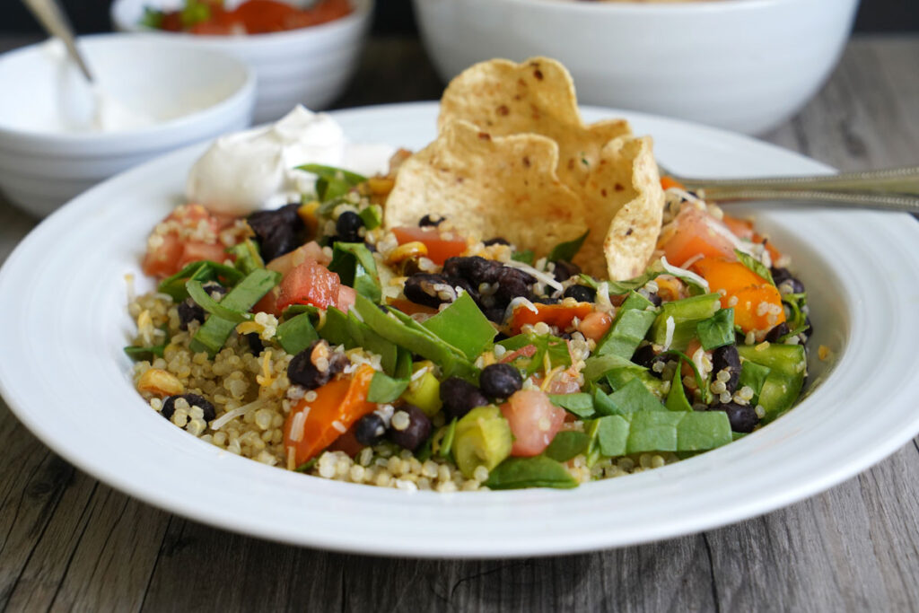 Quinoa Burrito Bowl after mixing ingredients, with tortilla chip and sour cream garnish.