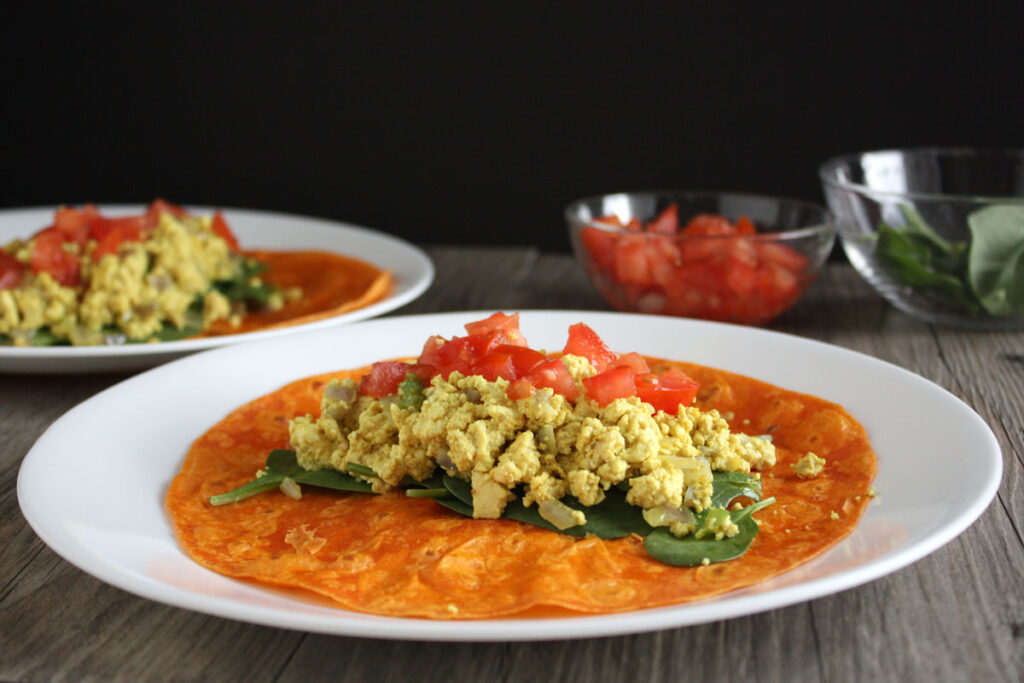 Tofu scramble wrap being assembled on plate.