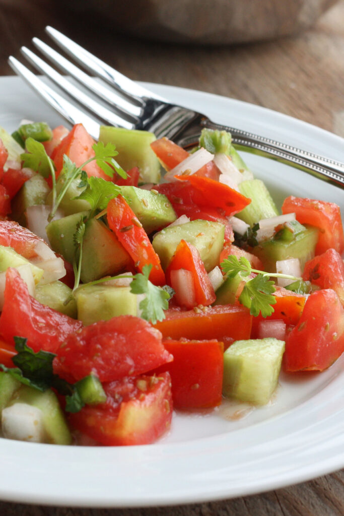 Close up view of tomato and cucumber salad in plate.