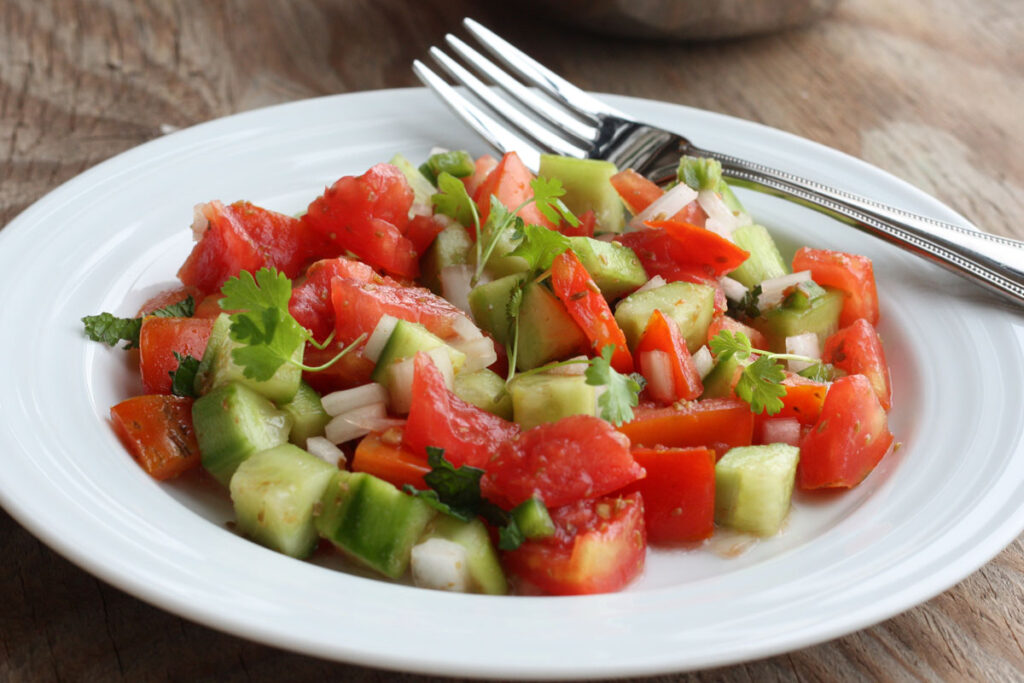 Cucumber tomato salad in a white plate with fork.