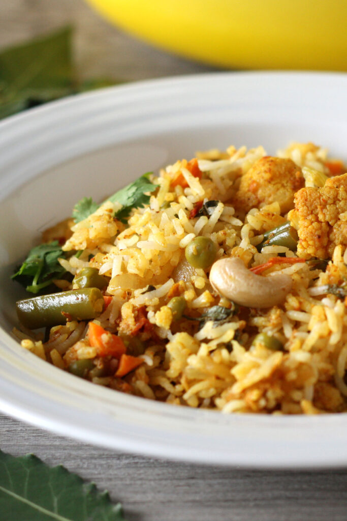 Closeup view of biryani showing rice, vegetables and cashews.