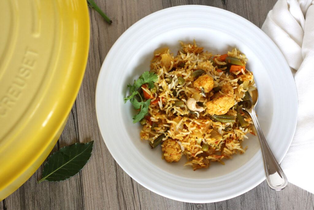 Top view of biryani in a white dish with spoon and napkin.