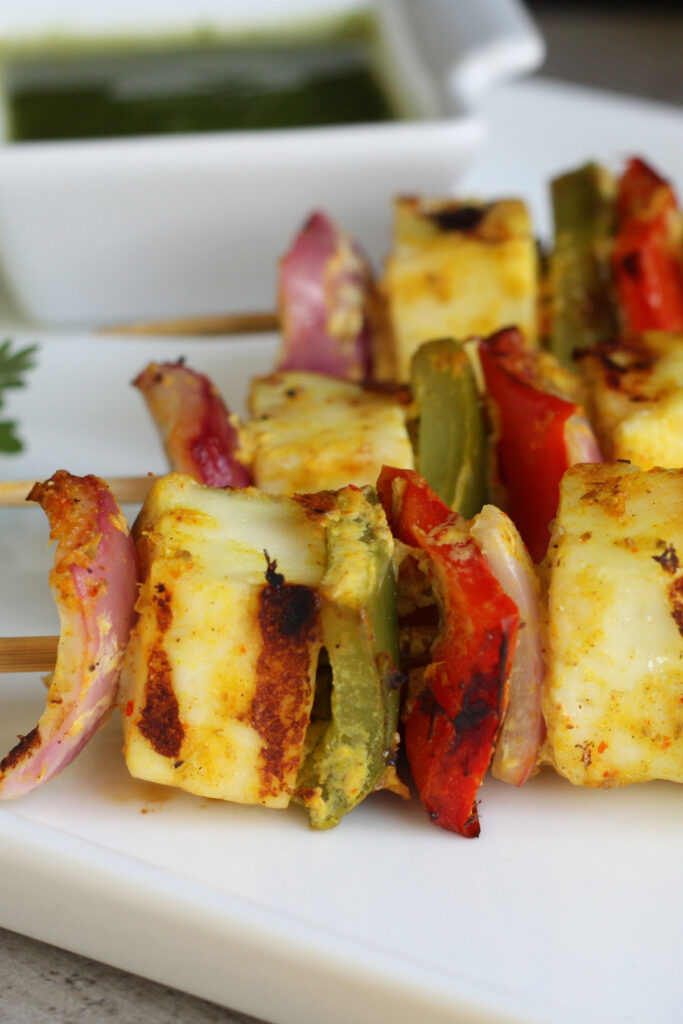 Close up of paneer vegetable kabobs on skewers.