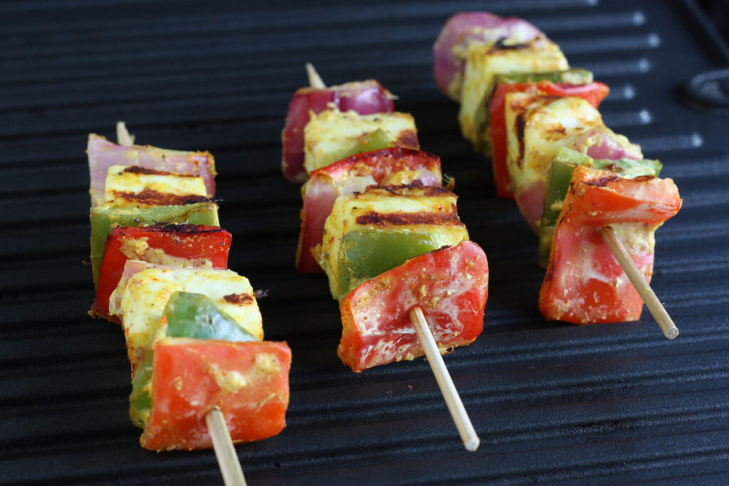 Vegetable and paneer on skewers on grill.