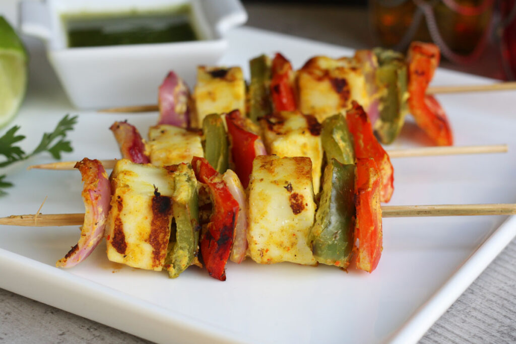 Finished paneer tikka on skewers in white plate with side of chutney.