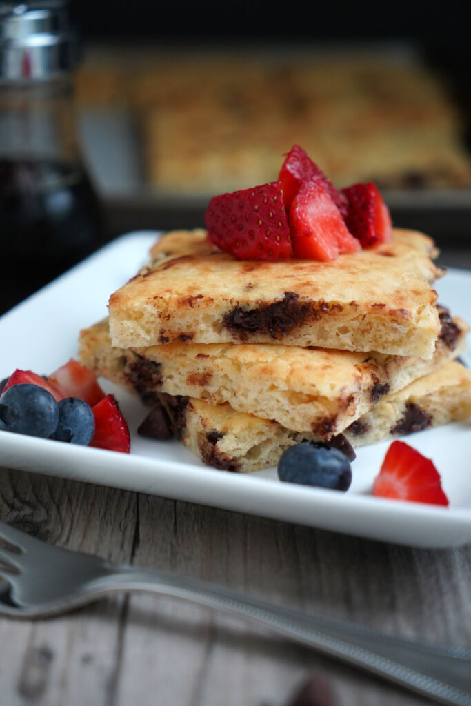 Sheet pan chocolate chip pancakes with berry toppings with in a white plate with fork.