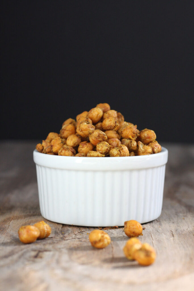 Spicy roasted chickpeas in white bowl with some  chickpeas out side bowl.