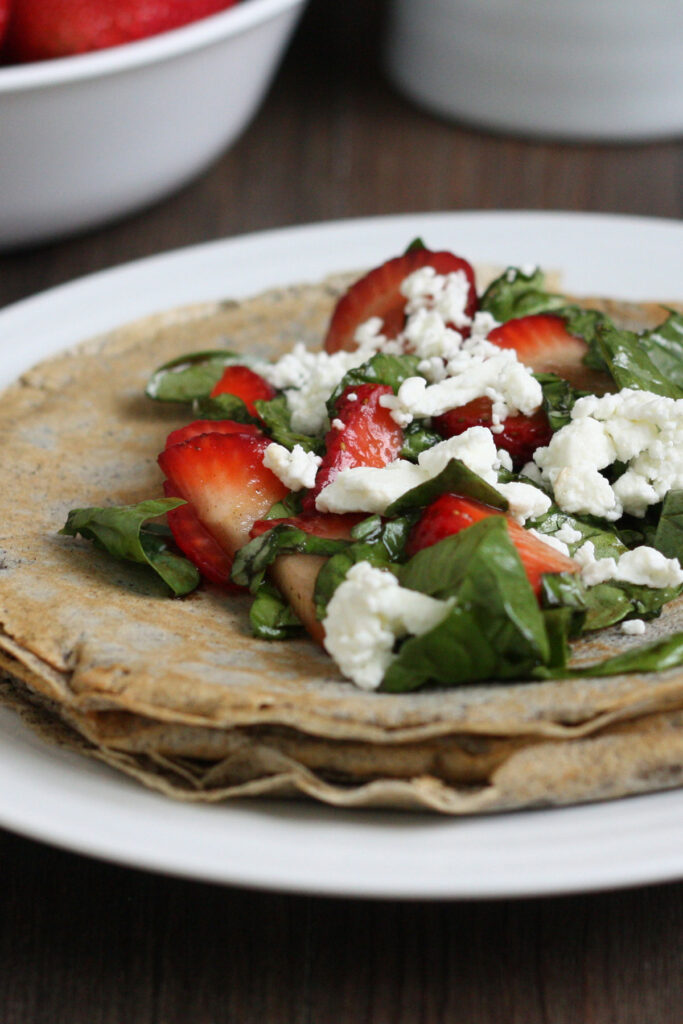 Strawberry, spinach, goat cheese and basil filling on top of  buckwheat crepe.